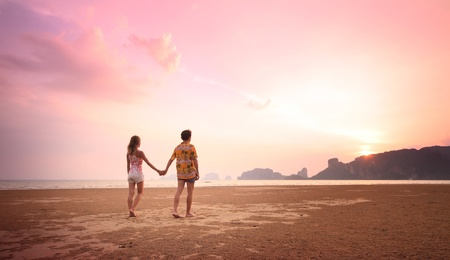 Young couple walking on a sandy coast