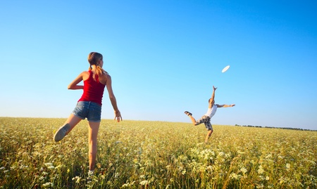 Foto de Young couple playing frisbee on a green meadow with grass on clear blue sky background - Imagen libre de derechos