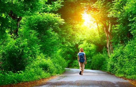 Foto de Woman with backpack walking on a wet road among green tropical trees - Imagen libre de derechos
