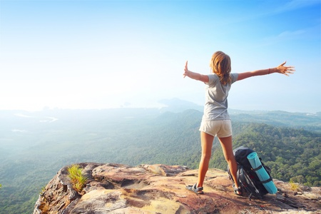 Foto de Young woman standing with backpack on cliff's edge and looking into a wide valley - Imagen libre de derechos