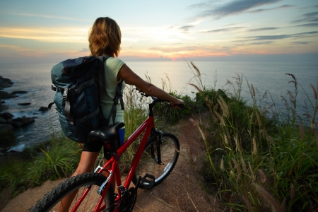 Female rider with backpack standing on top of a hill with her mountain bike and enjoying the sunset sea view