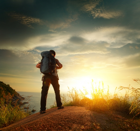 Hiker with backpack standing on a rock and enjoying sunset over sea
