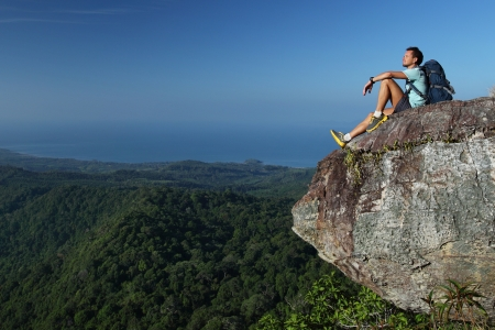 Young hiker relaxing on top of a mountain