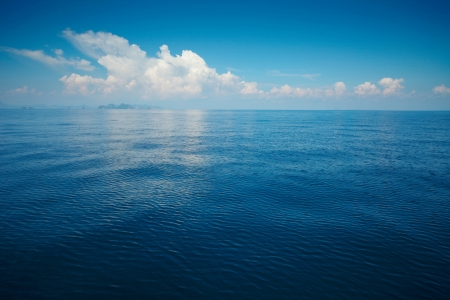 Photo pour Tropical rippled and calm sea with far islands on the horizon and white fluffy clouds - image libre de droit
