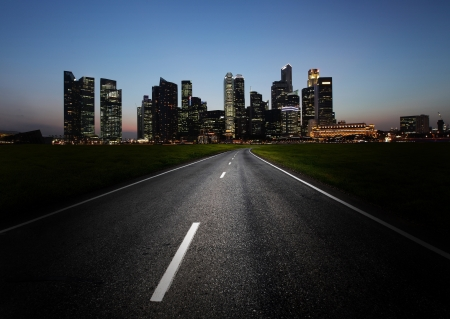 Asphalt road and a city with illuminated buildings on the horizon