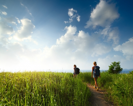Photo pour Hikers with backpacks walking through a meadow with lush grass - image libre de droit