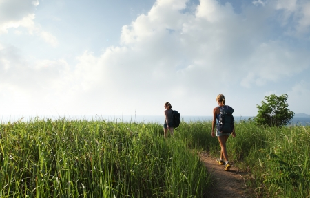Hikers with backpacks walking through tropical lush meadow