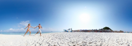 Panorama with young happy couple running on a sandy beach of tropical island at sunny day