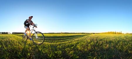 Foto de Young man cycling on a rural road through green spring meadow during sunset - Imagen libre de derechos
