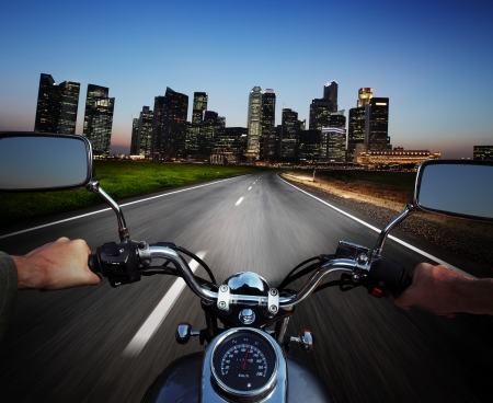 Driver riding motorcycle on an asphalt road at night towards big city