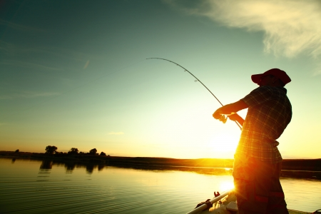 Photo pour Young man fishing on a lake from the boat at sunset - image libre de droit