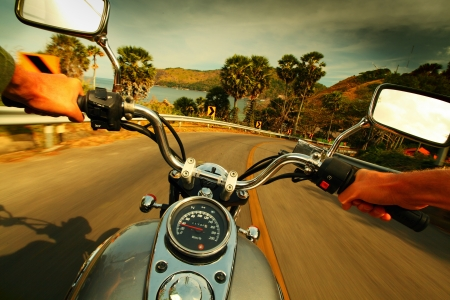 Driver riding motorcycle on an asphalt road in a tropics