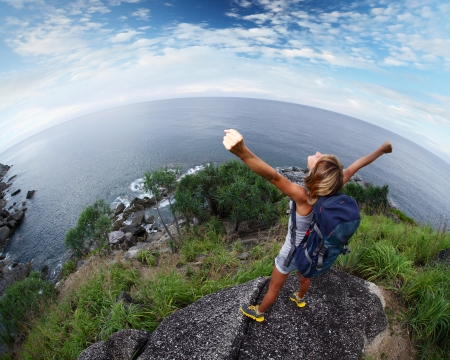 Hiker with raised hands standing on top of a mountain