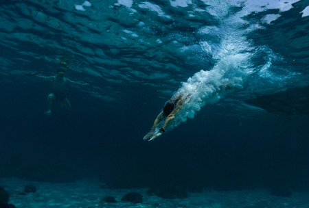 Photo pour Underwater shot of the man jumping into clear sea water - image libre de droit