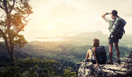 Foto de Hikers relaxing on top of the mountain and enjoying green valley view - Imagen libre de derechos