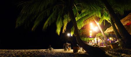 Photo pour Bar on a tropical beach among palm trees at night. Koh Chang, Thailand - image libre de droit