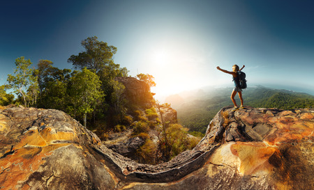 Photo pour Hiker standing on top of the mountain with raised hand - image libre de droit