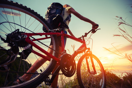 Photo pour Hiker with bicycle watching sunset - image libre de droit
