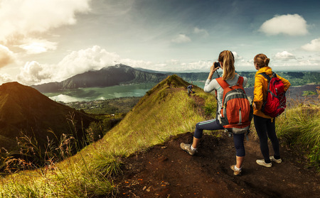 Two hikers with backpacks standing on top of the mountain enjoying valley view and taking a pictures