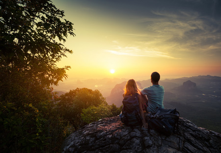 Foto de Two hikers on top of the mountain enjoying sunrise over the tropical valley - Imagen libre de derechos