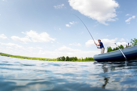 Photo pour Young man fishing on the fresh water pond at sunny day - image libre de droit