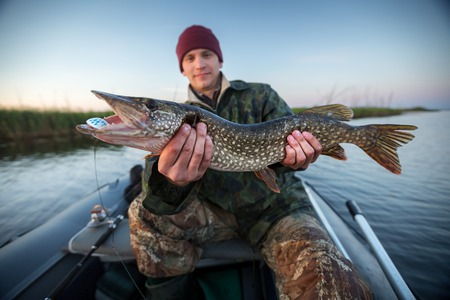 Photo pour Happy young fisherman holding pike and sitting in the boat on the lake - image libre de droit