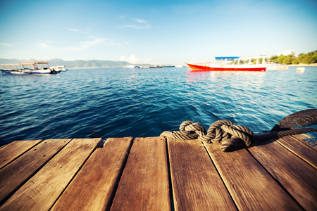 Wooden pier and calm tropical sea at sunrise. Focus on the rope
