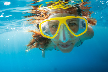 Photo pour Close up shot of the young lady snorkeling in the clear tropical sea - image libre de droit