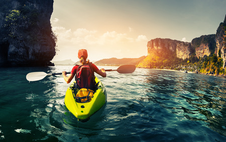 Photo pour Lady paddling the kayak in the calm tropical bay at sunset - image libre de droit