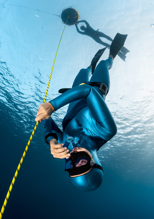 Photo pour Lady freediver descending along the rope her buddy watching on the surface by the buoy. Free immersion discipline - image libre de droit