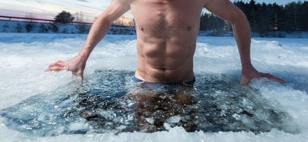Photo pour Young man bathing in the ice hole. Focus on the ice in a water only - image libre de droit