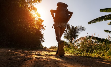 Hiker with backpack walking on the unpaved road at sunny hot day