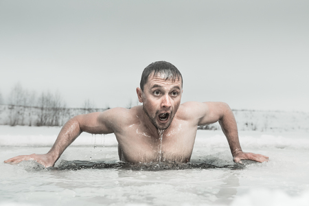 Photo pour Man swimming in the ice hole with emotional face - image libre de droit