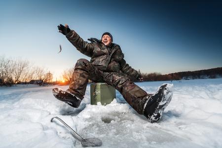 Foto de Happy fisherman with tiny fish on the winter lake - Imagen libre de derechos