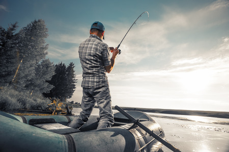 Photo pour Mature man fishing on the lake from inflatable boat - image libre de droit