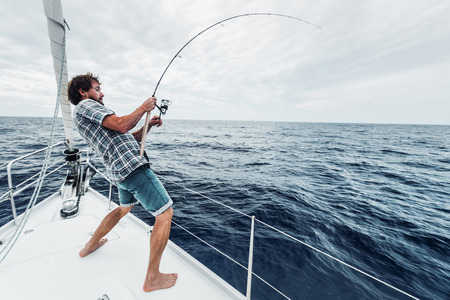 Photo pour Young man fishing hard in open sea from sail boat - image libre de droit