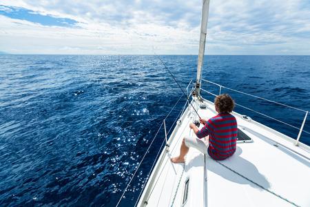 Photo pour Man fishing in a calm sea from a sail boat - image libre de droit