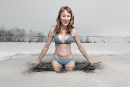 Photo pour Young lady going to swim in the ice hole - image libre de droit