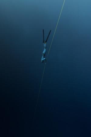 Photo pour Free diver descending along the rope in the depth - image libre de droit
