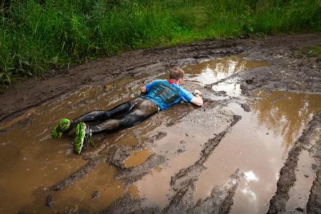 Foto de Athlete fall down to the dirty puddle in the rural road - Imagen libre de derechos
