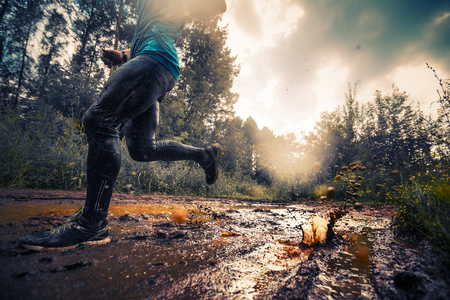 Foto de Trail running athlete moving through the dirty puddle in the rural road - Imagen libre de derechos