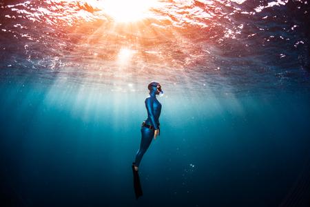 Photo pour Woman free diver ascending from the depth in a tropical clear sea - image libre de droit