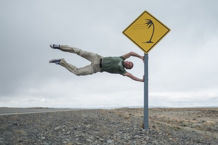 Foto de Man having fun with road sign set on the patagonian road in latitudes of Roaring Forties famous by its strong winds. Argentina - Imagen libre de derechos