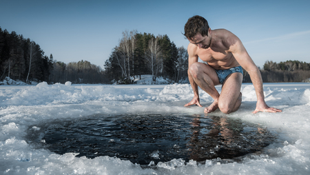 Foto de Young healthy man going to swim in an ice hole made in the winter lake - Imagen libre de derechos