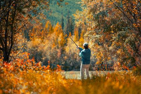 Photo pour Amateur angler fishing on the autumn river - image libre de droit