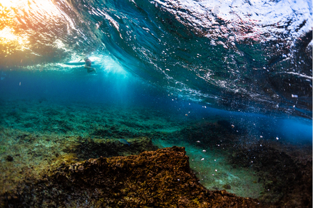 Photo pour Underwater view of the ocean wave breaking over the shallow reef with sharp stones. Surfer floats on the background - image libre de droit