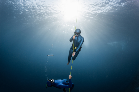 Photo for Two freedivers play with bubbles near the rope - Royalty Free Image