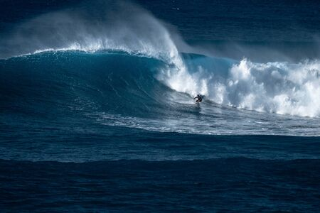 Photo pour Surfer rides giant wave at the famous Waimea Bay surf spot located on the North Shore of Oahu in Hawaii - image libre de droit