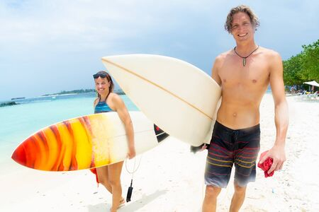 Photo pour Two happy surfers, caucasian man and woman smile and walk with their surf boards along the sandy beach after surf session. Both look at the camera. - image libre de droit