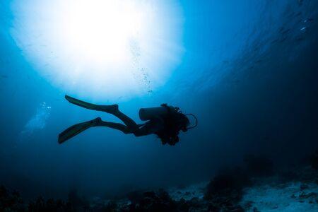 Photo pour Silhouette of the scuba diver swimming alone in the depth - image libre de droit